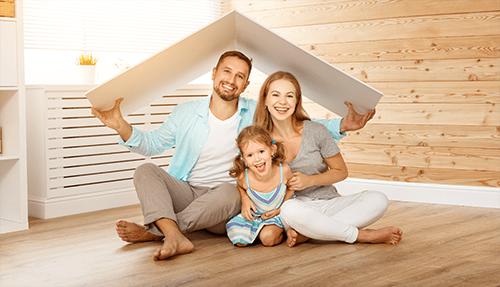 A family sitting on the floor in their new home