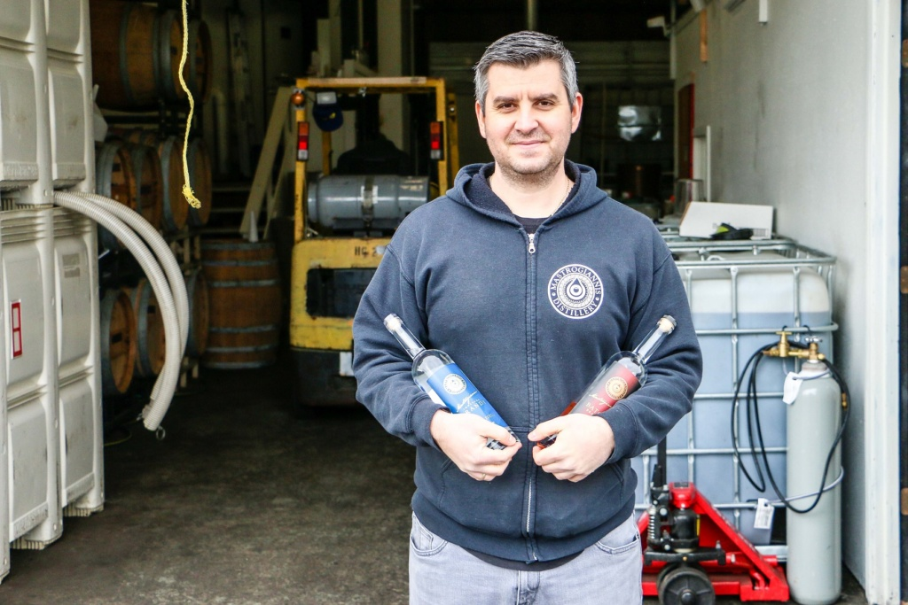 Mastrogiannis Distillery founder Ilias Mastrogiannis holding two bottles of his liquor in front of his craft distillery in Lakewood.