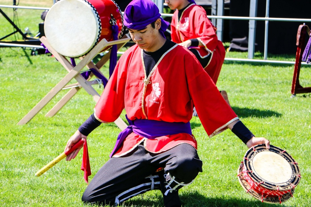 A young man in a bright red Japanese style shirt and purple headwrap holding a drum in his left hand and stick in his right hand, kneeling on the grass as he performs the opening ceremonies of Lakewood SummerFEST in Lakewood WA