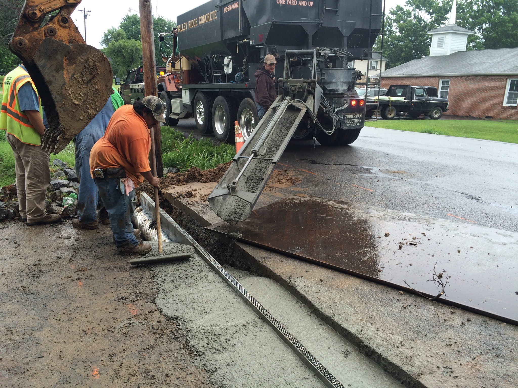 crew installing a new drainage system and pouring concrete