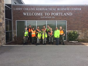 a group of people taking a photo under the Welcome to Portland Elevation 818, Larry Collins Aeronautical Business Center sign on the airport building.