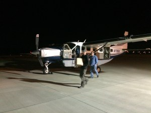 2 guys loading a plane at night at Portland Airport
