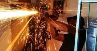 Un obrero desmonta u na máquina tragamoinedas en un colmado