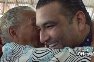 Luis Alberto escucha con atención a una anciana que le habla al oido
