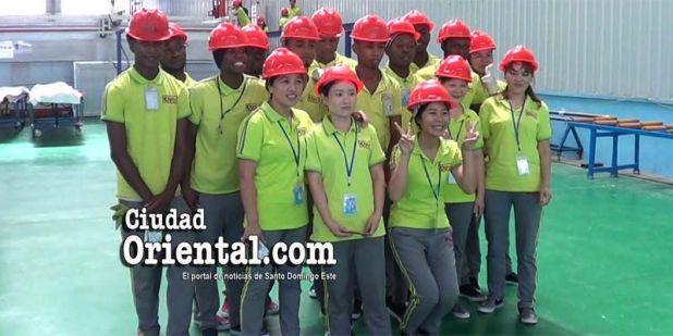 Obreros dominicanos, haitianos y chinos posan tras la inauguración de la empresa china