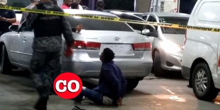 Uno de los presuntos asaltantes sentado en el pavimento