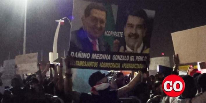 Un manifestante en la Plaza de la Bandera exhibe una pancarta contra Chávez y Maduro