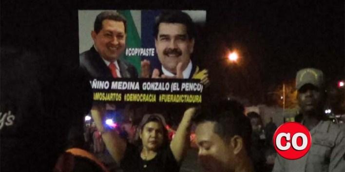Una manifestante en la Plaza de la Bandera exhibe una pancarta cintra Chávez y Maduro