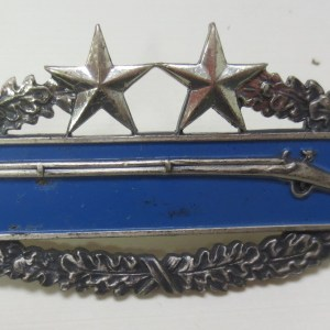 Badge with the symbol of shotgun at the center and stars on top