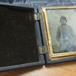 Opened case containing a frame of soldier's photo holding sword