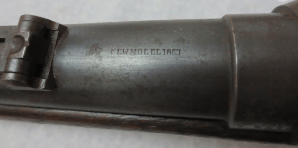 Part of the gun with numbers and letters carved