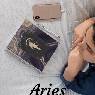 Image of woman lying on bed with a pink phone and black and gold Aries planner