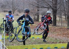 Race competitors carry their bikes over obstacles set up on the trail at the La Frost Cross race on Saturday, Dec. 3, 2016 in Mount Pleasant, MI.