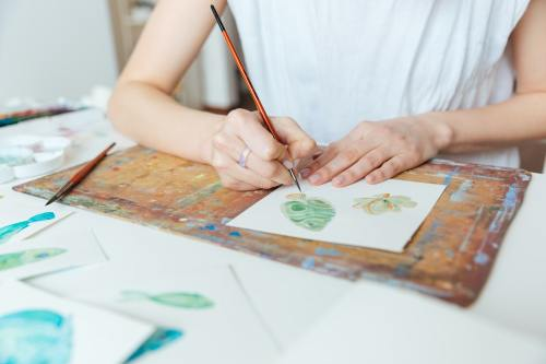 Hands of woman artist painting with paintbrush and watercolor paints