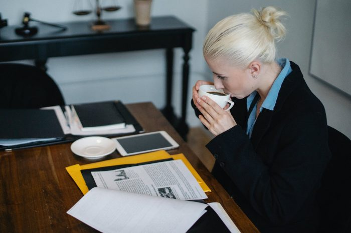 female solicitor drinking coffee while reading a case