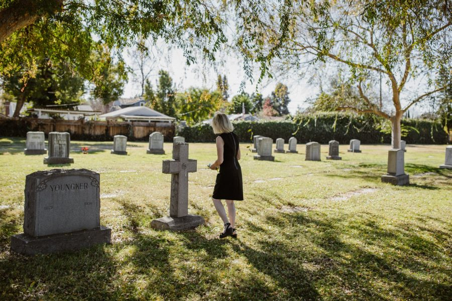 Widow standing at Grave thinking about Pension Rights
