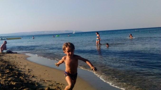 bambino che corre sulla spiaggia durante un weekend al mare in sicilia
