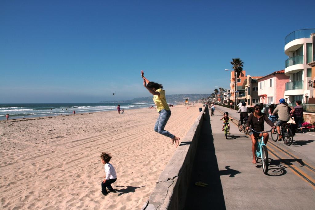 mamma e figlio che saltano in una spiaggia di San Diego