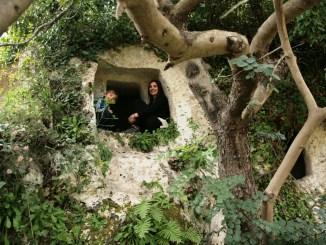 mamma e bambino dentro una grotta di Pantalica