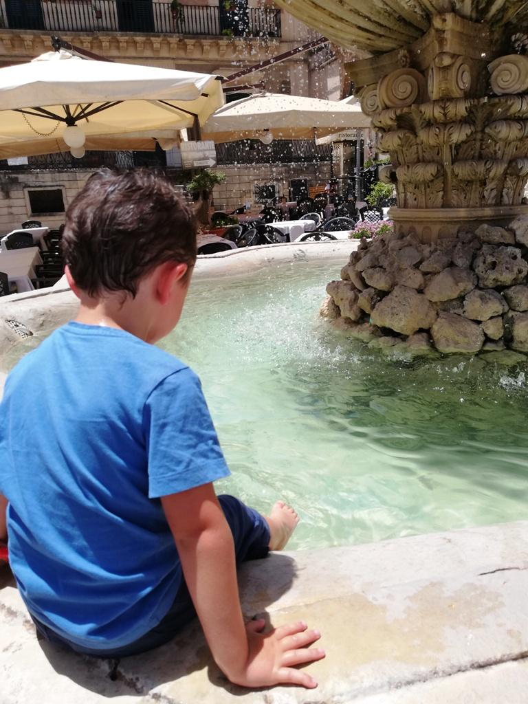 un bambino che si rinfresca in una fontana a Ragusa Ibla