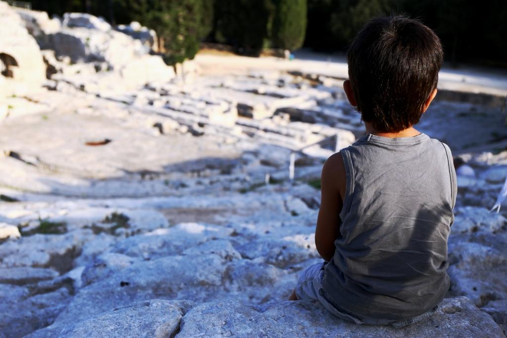 una bambino seduto al teatro greco di Siracusa
