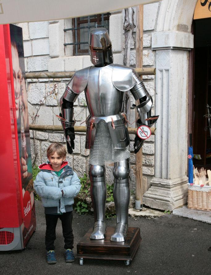 bambino vicino ad un'armatura al castello di predjama con i bambini