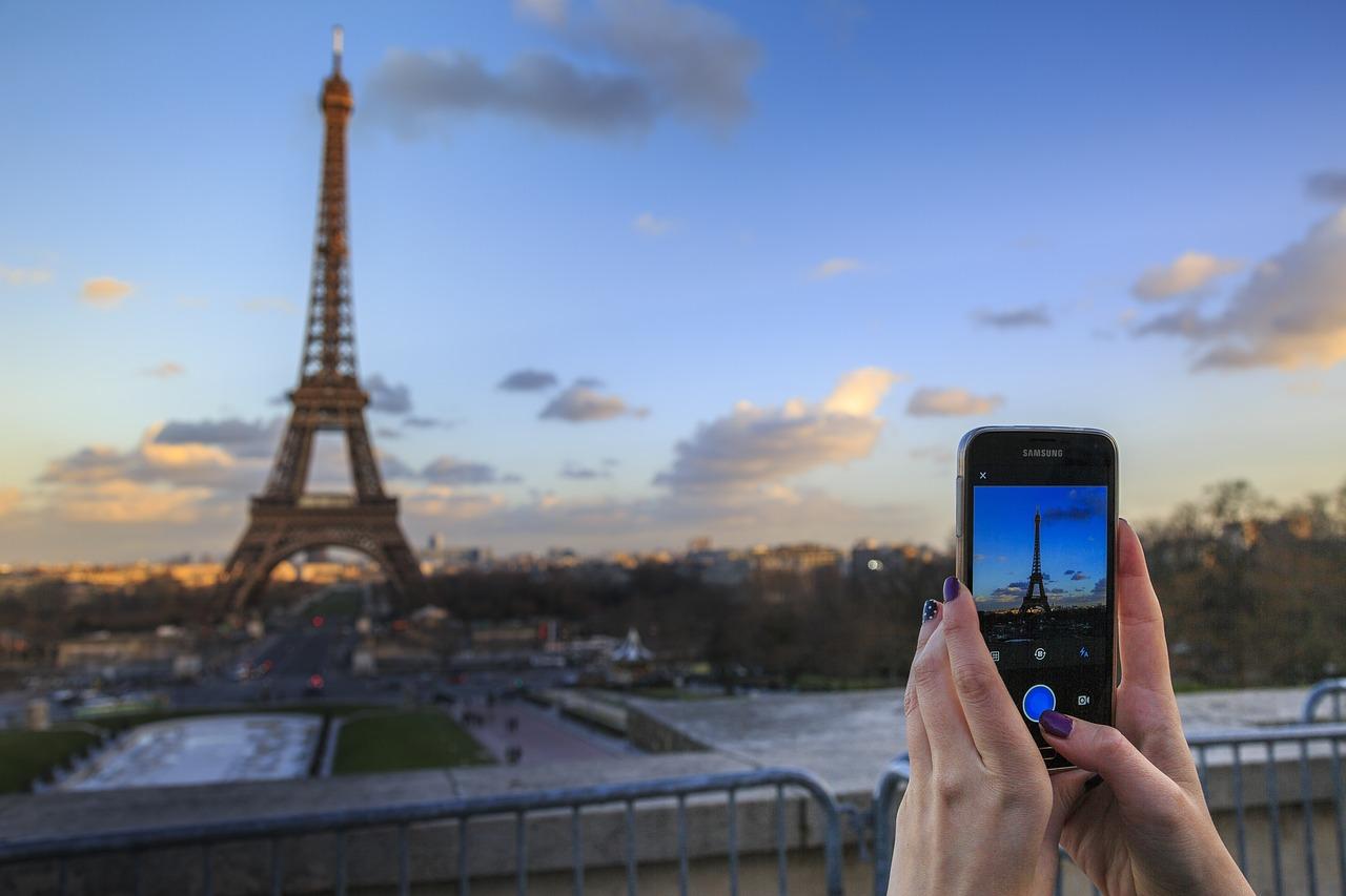 una donna che scatta una foto della tour eiffel