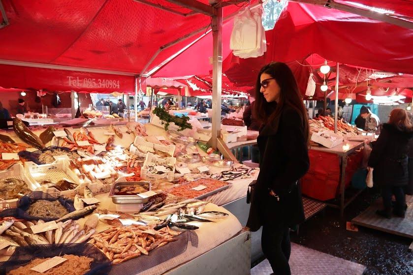 una ragazza al mercato del pesce di catania durante uno street food tour