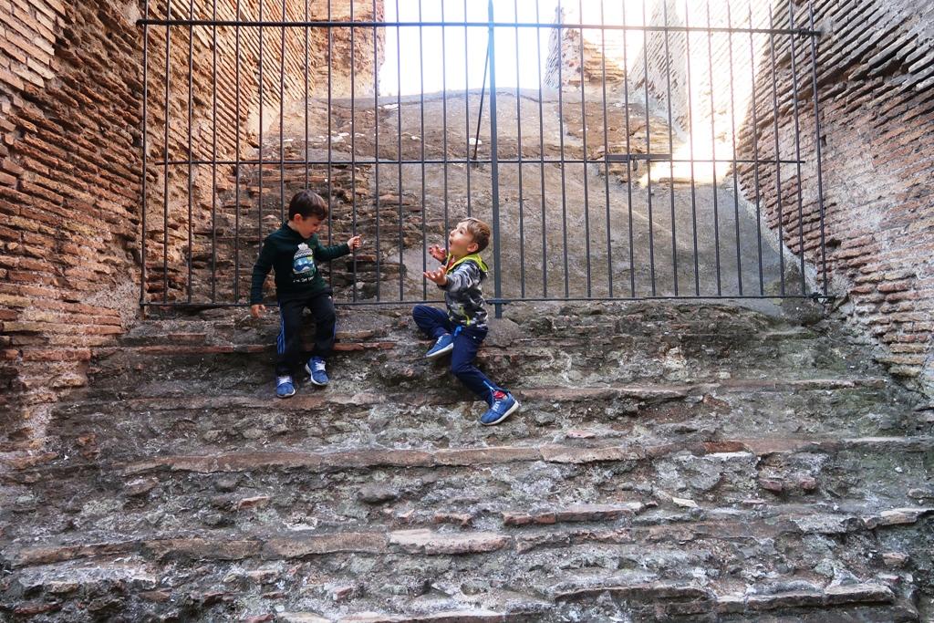 due bambini che giocano al Colosseo