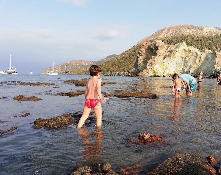 bimbo che gioca alla spiaggia di acque calde a Vulcano