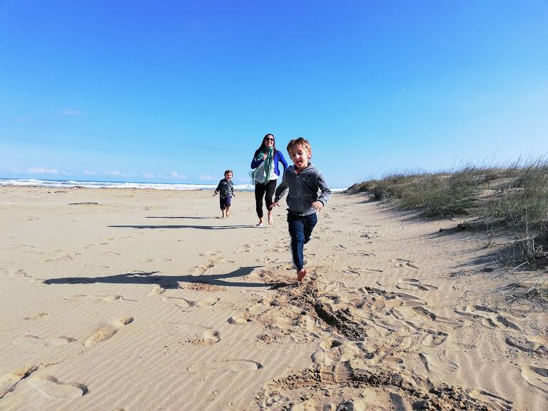 una famiglia che corre in una spiaggia in Sicilia