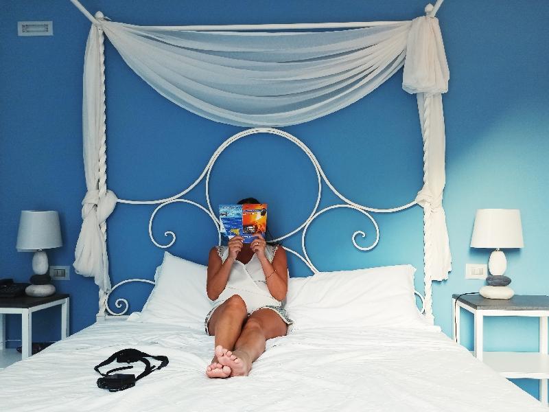 donna seduta sul letto di una camera d'hotel a Lipari