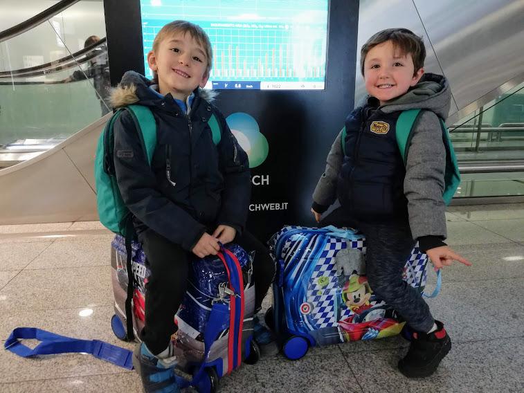 due bambini che viaggiano con trolley