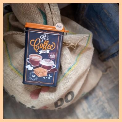 Boîte à café style vintage posée sur un grand sac en jute de café en grains Brésil