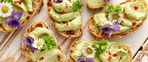 Canapes with avocado paste and edible flowers
