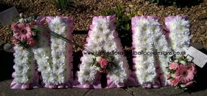 Flower covered letters spelling NAN as a funeral tribute