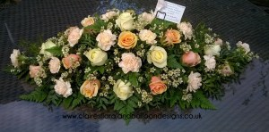 Peach and cream funeral coffin spray