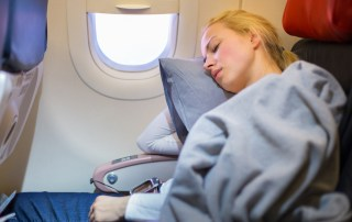 blonde woman sleeping on a plane