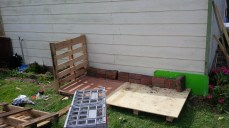 We secure a slatted pallet to one side of the floor to serve as the left hand wall.