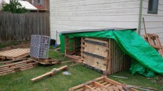We decided to splurge and spend an extra $10 on a plastic board to lay over the tarp. This would provide an extra layer of waterproofing, create a flatter surface, and prevent the tarp from flapping around too much. On the inside of the coup, we create a track using wood from the pallets, inside of which another pallet would be placed as a sliding door.