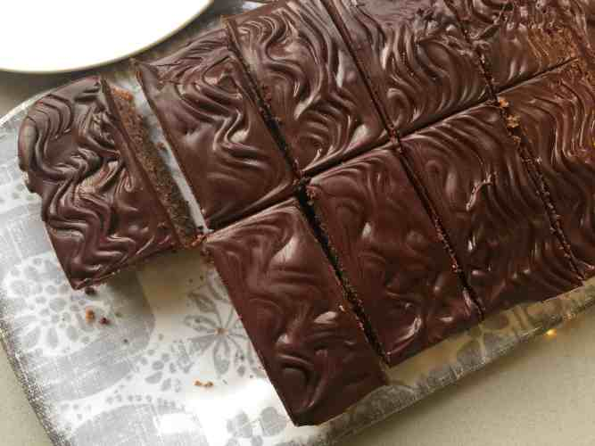 Slices of chocolate cake on a grey patterned tray.
