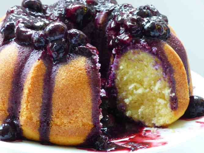 Vanilla Bundt Cake with a blueberry sauce on a white plate.