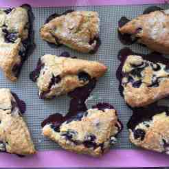 Baked blueberry scones on a baking tray lined with a silicone sheet.