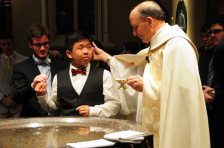 Fr. Peter Rocca, CSC, the rector of the Basilica, blesses Lin as he prepares to baptize him.