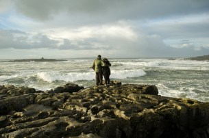 A couple watch the stormy seas brewing up at Doolin pier. Photograph by John Kelly.