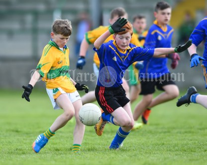Shane Morrissey of Carrigaholt/Moveen in action against Dara Cassidy of Carron/New Quay,Ballyvaughan/Fanore during their Primary Schools Div 3 Football 11-Aside final at Kilrush. Photograph by John Kelly