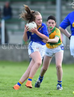 Emily Howard of Carron/New Quay,Ballyvaughan/Fanore in action against JJ Hickey of Carrigaholt/Moveen during their Primary Schools Div 3 Football 11-Aside final at Kilrush. Photograph by John Kelly