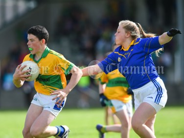 JJ Hickey of Carrigaholt/Moveen in action against Emily Howard of Carron/New Quay,Ballyvaughan/Fanore during their Primary Schools Div 3 Football 11-Aside final at Kilrush. Photograph by John Kelly