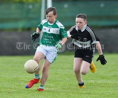 Corey O Sullivan of Kilrush in action against Micheal Honan of Doonbeg during their Primary Schools Div 2 Football 13-Aside final at Kilrush. Photograph by John Kelly