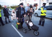 A Garda pushes a pram for a family as she escorts them through the secure area into Doonbeg Village ahead of the walkabout by Eric and Don Junior Trump. Photograph by John Kelly